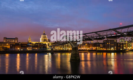 Red skies and stunning light reflections at dusk on the Millennium Bridge at Bankside, London, UK. - Stock Photo
