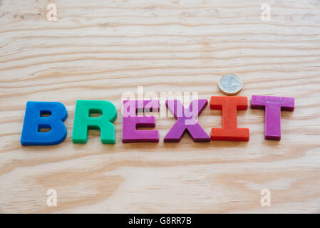 Colorful brexit text on wooden background with euro coin - Stock Photo