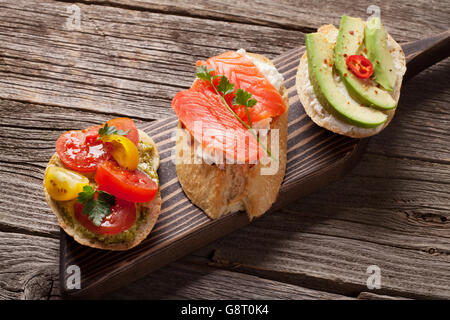 Toast sandwiches with avocado, tomatoes and salmon on wooden background - Stock Photo