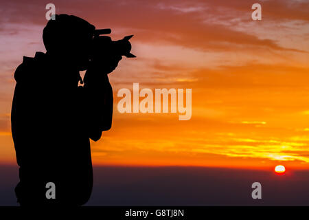 Silhouette of Photographer on Hilltop in beautiful clouds - Stock Photo