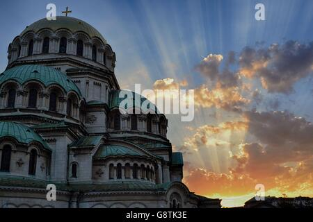 Aleksander Nevsky Cathedral at sunset (Sofia, Bulgaria) with heaven-like rays coming out of the clouds - Stock Photo
