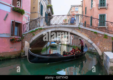 Rio dei Santi Apostoli, Cannaregio, Venice, Italy: a gondola glides under the Ponte San Canzian - Stock Photo