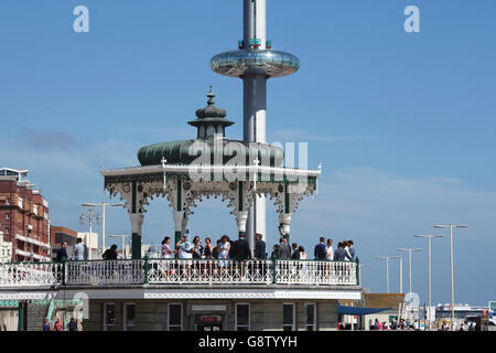 Old and new attractions on Brigton seafront: the old bandstand (with party!) and the new i360 moving observation - Stock Photo