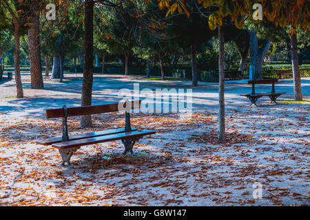 View Of Wooden Benches In Park Against Trees - Stock Photo