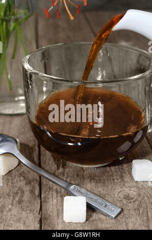 Strong tea is poured into a cup - Stock Photo