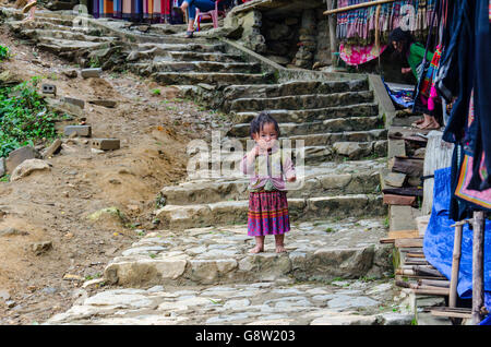 Little Vietnamese kid belonging to the Black Hmong minority, dressed in traditional clothes in Cat Cat village, - Stock Photo
