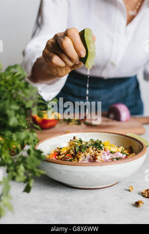 A woman is photographed while she was squeezing lime into a bowl of peach and walnut salsa photographed from the - Stock Photo