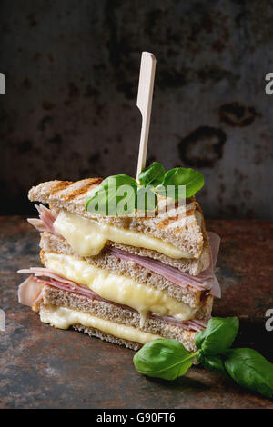 Whole grain grilled sandwich bread with melting hot cheese, ham and basil over dark rusty iron textured background. - Stock Photo
