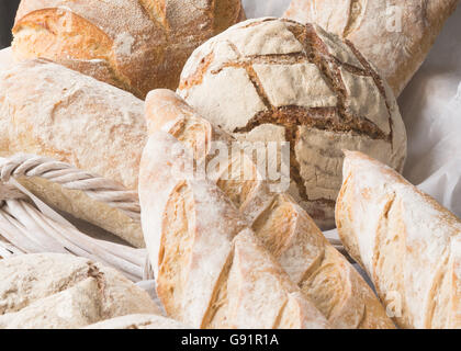 freshly baked artisan loaves of bread in white wicker basket - close up - Stock Photo