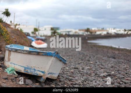Playa Quemada boat on the stony beach looking towards the small fishing village, Lanzarote - Stock Photo