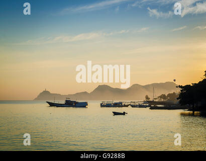 boats at harbour in dili coast east timor at sunset - Stock Photo