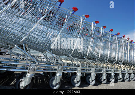 Shopping carts in a stack against a clear blue sky - Stock Photo
