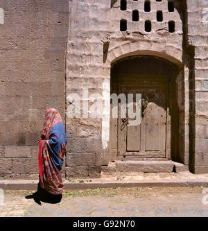 A veiled Muslim woman walks on a Sana'a street, Yemen. At background typical Yemen houses. - Stock Photo