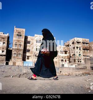 Veiled Muslim woman walks on  Sana'a street, Yemen. At background typical Yemen houses. - Stock Photo