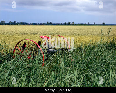 abandoned historical agricultural machinery in a field - Stock Photo