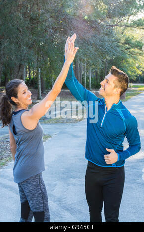 Young Hispanic Spanish couple competition victory celebrate fun raised arms winning contest Model Released, MR-14, - Stock Photo