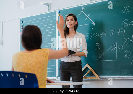 Teacher or docent or educator giving while lesson in front of a blackboard or board a sheet of paper and educate - Stock Photo