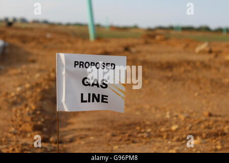 A Gas Line in a New Housing Construction Zone.  A Flag in Front of Dirt, Grass, Trees, Sky, Rocks, and Pipe - New - Stock Photo
