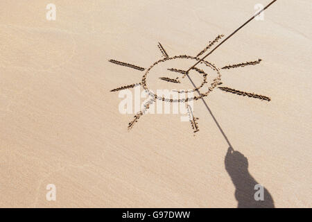 Shadow hand holding a stick drawing a smiley face sun on a beach. UK - Stock Photo