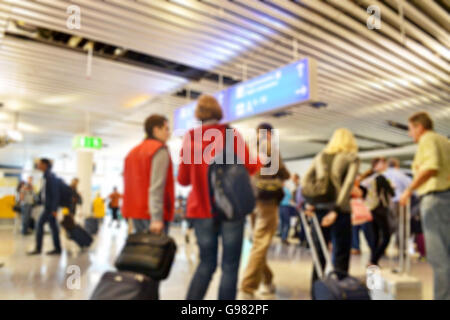 Blurred background of a very busy European international airport during the day - Stock Photo