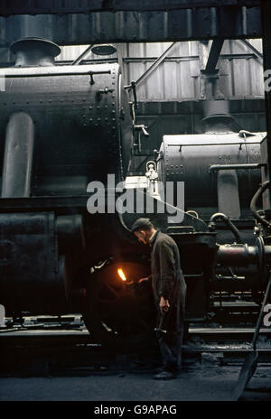 A fitter complete with oil lamp and hammer undertakes a repair to an ex-LMS Stanier 8F Class 2-8-0 at Rose Grove - Stock Photo