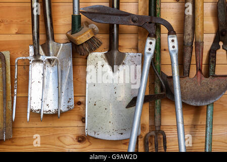 Garden tools hanging in a wooden shed. - Stock Photo
