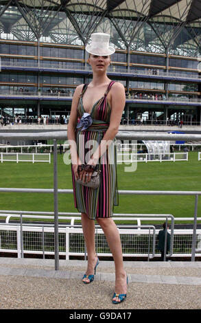 Model Jodie Kidd poses in a rainbow-striped low-cut dress by Missoni and white mini-top hat decorated with crystals by Cozmo Jenksfront in front of the new grandstand at Royal Ascot, Berkshire.