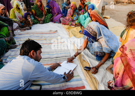 INDIA, Madhya Pradesh , microcredit, rural woman saving bank in village, illiterate uneducated women sign with thumb - Stock Photo