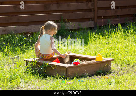 little girl sitting back playing in a sandbox - Stock Photo