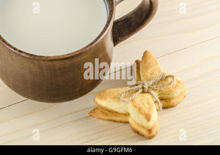 Butterfly cookies and cap of milk on wooden background - Stock Photo