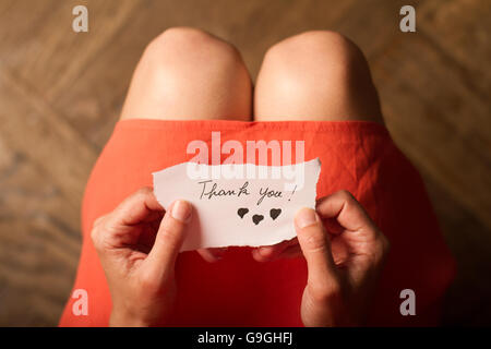 Top view of a woman with pink dress holding a thank you note in her hand - Stock Photo