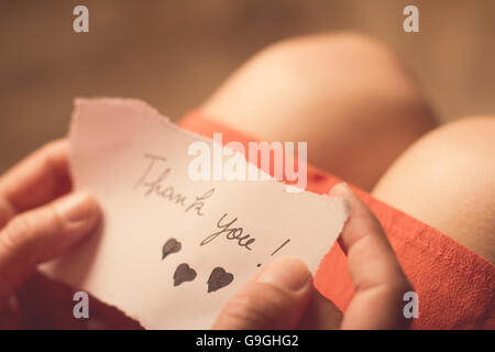 Top view of a woman with pink dress holding a thank you note in her hand with shallow depth of field - Stock Photo