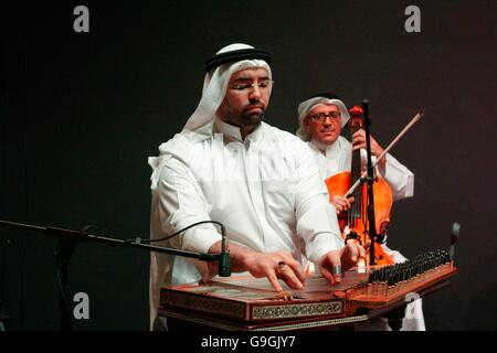 Musician of the Mohammed bin Faris Ensemble plays qunan zither at traditional sawt music concert in Al Khalifa Centre, - Stock Photo
