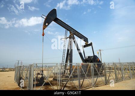 Pumpjack aka oil horse, nodding donkey, oil jack, beam pump raises crude oil in the Bahrain desert at Sakhir on - Stock Photo