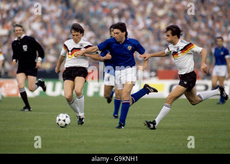 Italy's Carlo Ancelotti (c) tries to burst between West Germany's Lothar Matthaus (l) and Thomas Berthold (r) - Stock Photo