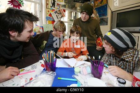 Members of McFly (left to right) Harry Judd, Dougie Poynter, Tom Fletcher and Danny Jones help Fergus Hunt, age - Stock Photo