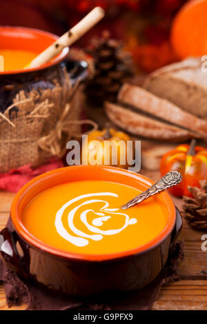 A bowl of homemade creamy pumpkin soup on a rustic table with autumn decorations.