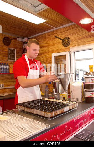 Man making Poffertjes, typical small pancakes, on the Albert Cuypmarket in downtown Amsterdam, Netherlands in spring. - Stock Photo