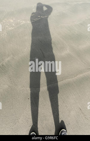 a shadow cast on the beach facing the ocean - Stock Photo