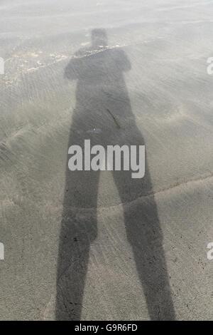 a shadow cast on the beach facing the ocean - Stock Photo