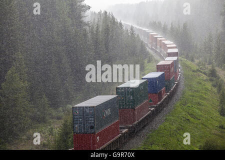 Cargo train with containers traveling through Rocky Mountains Rockies, Canada, North America - Stock Photo