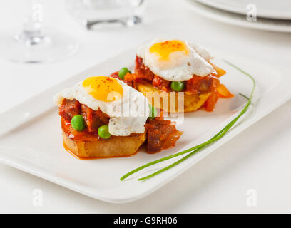 Chorizo and fried egg on a potato slice. Small plate for sharing. - Stock Photo