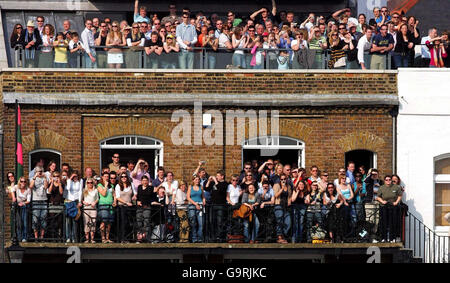 Supporters cheer on the Oxford and Cambridge University rowing teams at Hammersmith during the 153rd Boat Race today.