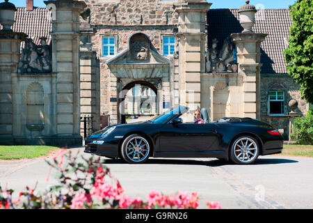 stylish woman and Porsche 911 in front of castle, 911 carrera, 4S, convertible car, sportscar, luxurious - Stock Photo