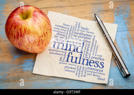 mindfulness word cloud on a napkin with a fresh apple - Stock Photo