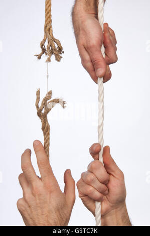 Frayed rope pulled by hand - Stock Photo