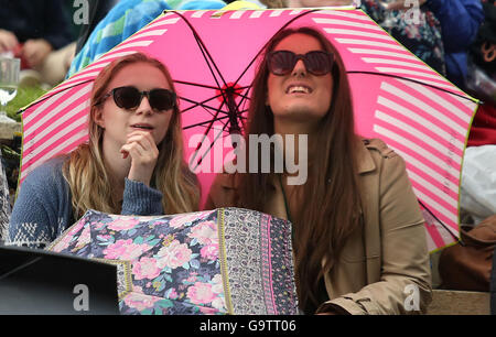 Spectators shelter from the rain on Murray Mound on day five of the Wimbledon Championships at the All England Lawn - Stock Photo