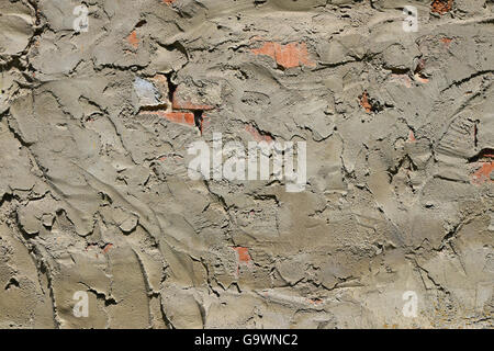 Cement uneven rough plastering layer on unfinished brick wall of construction site - Stock Photo