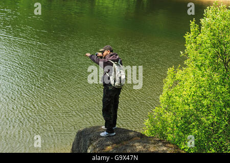 man on a rock above the water in a position to jump - Stock Photo