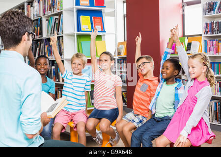 Kids raising their hands in library - Stock Photo